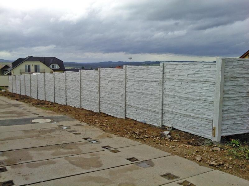 Šedý okrasný betonový plot v mírném svahu
