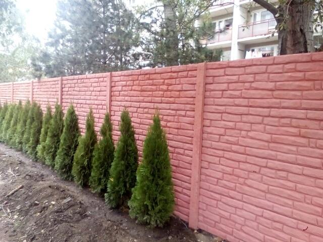 Betonový plot v červené barvě kolem cesty