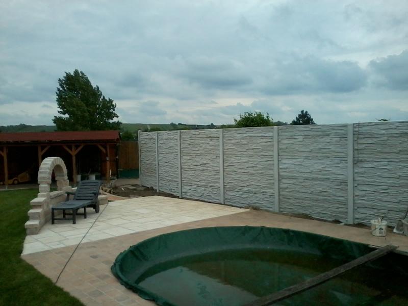 Neprůhledný betonový plot kolem bazénu