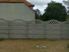 Částečně průhledný betonový plot s horní obloukovou betonovou deskou