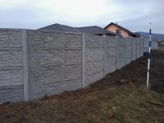 Obestavěný pozemek novostavby betonovým plotem