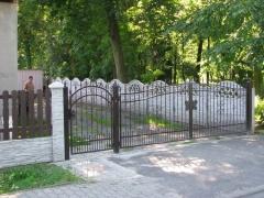 Betonový okrasný plot s kovovou černou bránou