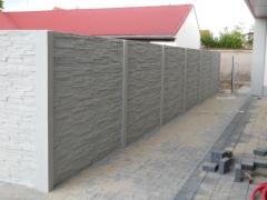Betonový plot podél chodníku v šedém dekoru cihliček
