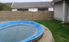 Neprůhledný betonový plot kolem zahradního bazénu