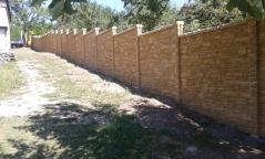 Neprůhledný plot z betonu tónovaný do několika odstínů připomínající přírodní obkladový kámen
