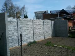 Šedý betonový plot z betonových desek v dekoru cihliček a obloukovou horní deskou