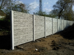 Panelový šedý betonový plot kolem zahrady